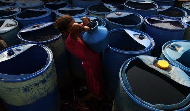 A girl collects water from buckets filled by the local municipal authorities, Mumbai, 26 May, 2014. People in the area still have to pay for clean drinking water as there is no proper purification system in place.
