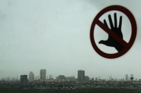 """Mumbai highrise seen through a monorail window with a """"No touching"""" sticker on it, Mumbai, 6 August, 2014. According to media reports the untouchable prices of residential homes in the last fiscal year have led to decreased demands of property in the last one year."""