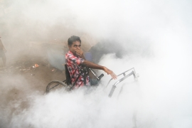 A man sits in his wheelchair as he is surrounded by fumes during a routine fumigation process by the BMC, Mumbai, India.