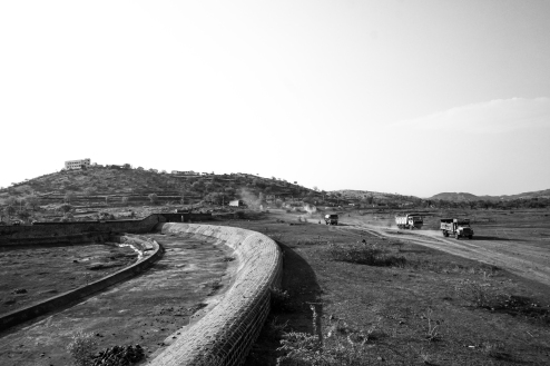 Trucks ply on the empty reservoir of Bendsura Dam, Beer, Maharashtra 2016.
