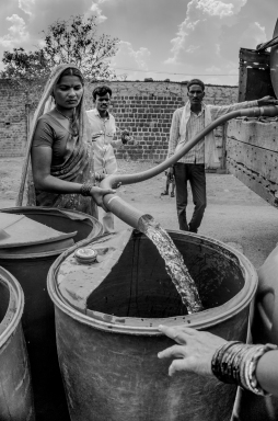 A woman fills a barrel of water from a water tuck provided by the government, Maharashtra 2016. These trucks visit the villages twice every week.